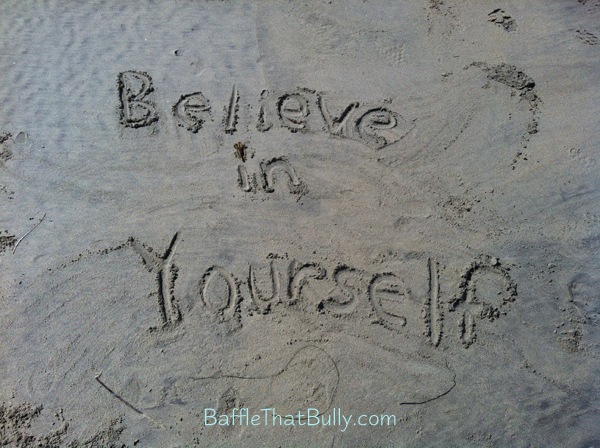 Confidence building quote written in sand at beach: Believe in Yourself!